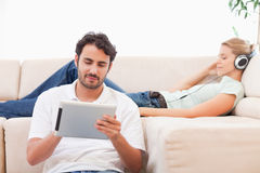 Man using a tablet computer while his girlfriend is listening to music Royalty Free Stock Photo