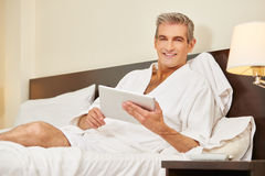 Man using tablet computer in hotel room Stock Photos
