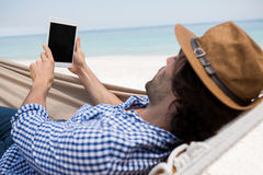 Man using tablet computer while lying in hammock Royalty Free Stock Photos