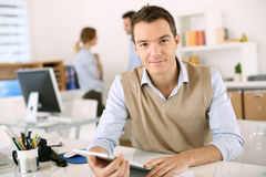 Man using tablet and computer in office Stock Images