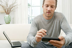 Man using tablet and computer on sofa at home. Young entrepreneur using technology while sitting on a white sofa at home Stock Photography