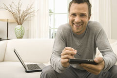 Man using tablet and computer on sofa at home. Young professional man sitting down on home's sofa, using technology and smiling at the camera Royalty Free Stock Images