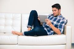 Man using tablet computer on the sofa Stock Photos