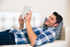 Man using tablet computer on the sofa Stock Images