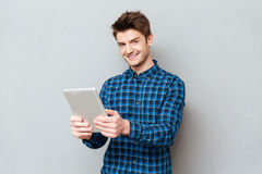 Man using tablet computer for work. Cheerful man looking camera while working with tablet computer over grey royalty free stock images