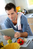 Man using tablet before cooking royalty free stock photography