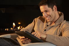 Man using tablet in front of fire at home Royalty Free Stock Photography