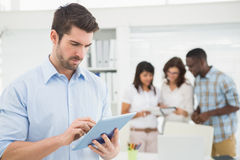 Man using tablet in front of his colleagues Royalty Free Stock Images