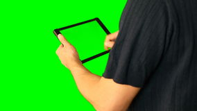 Man using tablet with green screen doubled on big screen. Male hold tablet in hand and make any gestures with fingers. Tap swipe scroll zoom in and out retate stock video