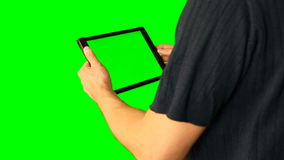 Man using tablet with green screen doubled on big screen. Male hold tablet in hand and make any gestures with fingers. Tap swipe scroll zoom in and out retate stock footage