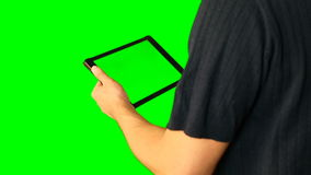 Man using tablet with green screen doubled on big screen. Male hold tablet in hand and make any gestures with fingers. Tap swipe scroll zoom in and out retate stock video footage