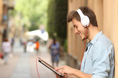 Man using a tablet with headphones on the street Stock Photography