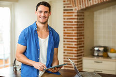 Man using tablet in kitchen Stock Photography