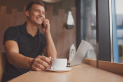 Man using tablet, laptop and cellphone while drinking coffee Royalty Free Stock Photo