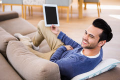Man using tablet lying on the couch Royalty Free Stock Photo