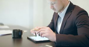 Man using tablet in Office finance background. Young Man Using Digital Tablet in Office. Shoot on sony FS7 stock footage