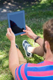 Man using tablet in the park Stock Photo