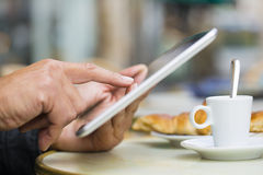Man using a Tablet Pc on cafe terrace, croissant and coffee Royalty Free Stock Photography