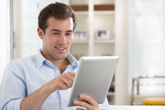 Man using tablet pc on couch at home Royalty Free Stock Image