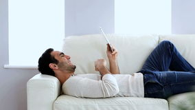 Man using a tablet pc on the couch. Man using a tablet pc while he is laid on the couch stock video footage