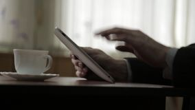 Man using tablet PC and drinking coffee. Close-up hands on a window background stock video