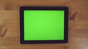 Man Using Tablet PC with Green Screen. On a Wooden Background.Horizontally stock video