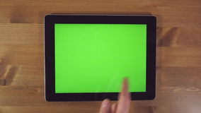 Man Using Tablet PC with Green Screen. On a Wooden Background.Horizontally stock video footage