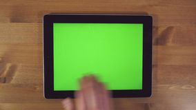 Man Using Tablet PC with Green Screen. On a Wooden Background.Horizontally stock footage