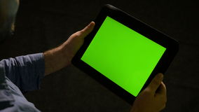 Man using a tablet pc with green screen and zooming in and out on the display. Man using tablet pc with green screen and zooming in and out on the display stock footage