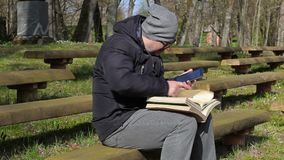 Man using tablet PC and reading books on bench in park stock video footage
