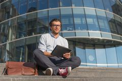 Man using tablet pc sitting on stairs near modern glass building stock images