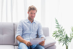 Man using a tablet while he is sat on the couch Stock Photos