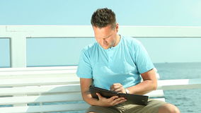 Man using tablet by sea Stock Photography