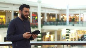 Man using tablet in shopping mall. Lot of people at the background.  stock video footage