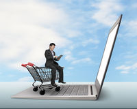Man using tablet sitting on shopping cart with laptop Royalty Free Stock Photo