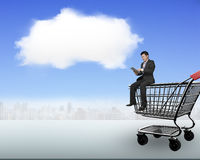 Man using tablet sitting on shopping cart with white cloud Royalty Free Stock Image