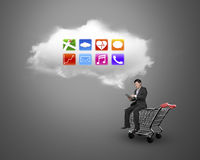 Man using tablet sitting on shopping cart with white cloud Royalty Free Stock Images