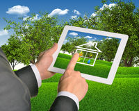 Man using tablet with symbols of public service. Man using tablet pc with symbols of public service and house. Landscape as backdrop Stock Photo