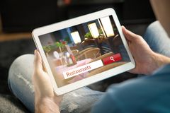 Man using tablet trying to find the perfect restaurant. From review website or application. Tavern, cafe or bistro search engine and app online. Rating social Royalty Free Stock Images