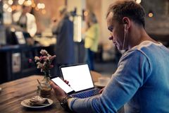 Man using tech gadgets in cafe. While listening music royalty free stock photography
