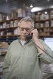 Man Using Telephone In Warehouse Stock Image