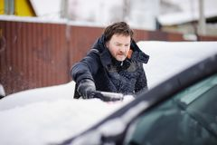 Man using tool for cleaning his car from snow Royalty Free Stock Photos