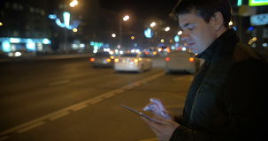 Man using touch pad by the busy road in city. Young man standing by the road with intense traffic in the evening. He using tablet computer to type a message stock video footage