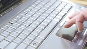Man using touchpad on notebook keyboard with his finger with blue light tint.  stock video footage