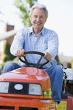 Man using tractor. Senior man using a tractor/lawn mower cutting the grass Royalty Free Stock Image