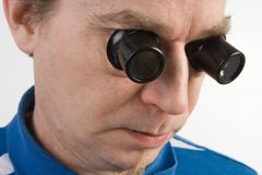 Man using two magnifying loupes Stock Images