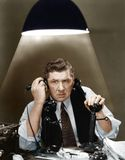 Man using two telephones Stock Images