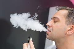 Man using vapourizer as smoking alternative. Enjoying stock photos
