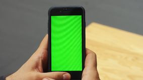 Man using vertical smartphone with green screen. Close-up shot of man`s hands with mobile phone. Chroma key. Close up. Vertical stock footage
