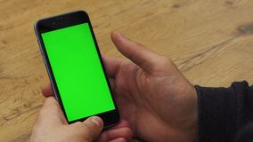 Man using vertical smartphone with green screen. Close-up shot of man`s hands with mobile phone. Chroma key. Close up. Vertical stock video footage